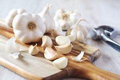 Bulbos do alho na placa de corte e na imprensa de alho fotografia de stock