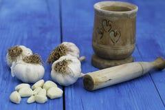 Bulbos e cravos-da-índia do alho com almofariz de madeira Foto de Stock Royalty Free