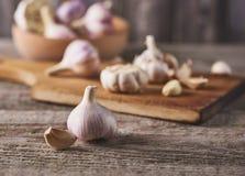 Bulbos e cravos-da-índia frescos do alho na placa de corte fotografia de stock royalty free