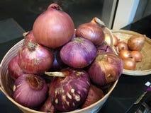 Bulbos orgánicos frescos de la cebolla blanca y chalote rojo entre muchos fondo de la cebolla y del chalote en cesta en supermerc foto de archivo libre de regalías
