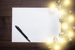 Bulbos que brillan intensamente y hoja en blanco del papel Fotos de archivo libres de regalías