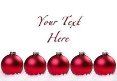 Bulbos rojos brillantes de la Navidad en la nieve Imágenes de archivo libres de regalías