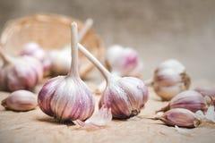 Bulbos y clavos del ajo orgánico natural en un papel del arte y en una cesta hecha en casa fotos de archivo