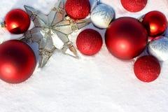 Bulbos y estrella rojos de la Navidad en la frontera blanca de la nieve Imagen de archivo