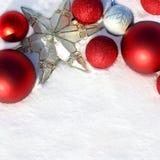 Bulbos y estrella rojos de la Navidad en la frontera blanca de la nieve Fotografía de archivo