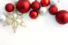 Bulbos y estrella rojos de la Navidad en la frontera blanca de la nieve Fotos de archivo libres de regalías
