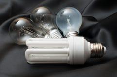 Bulbs. Energy Saving Bulb and Three Aged Burnt Tungsten Bulbs on Black Background royalty free stock photography