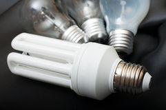 Bulbs. Energy Saving Bulb and Three Aged Burnt Tungsten Bulbs on Black Background Royalty Free Stock Images