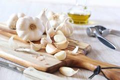 Bulbs of garlic, garlic press and olive oil Royalty Free Stock Photos