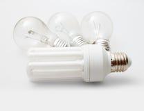 Bulbs. New Energy Saving Bulb and Three Aged Burnt Tungsten Bulbs on Light Background stock image