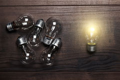 Bulbs uniqueness concept on wooden background royalty free stock images
