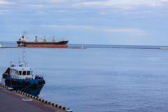 bulck Schiff im Seehafen und im Schleppseilboot Lizenzfreie Stockfotos
