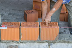 Bulder worker laying hollow clay block Stock Image