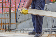 Bulder worker sawing wood board with hand saw 3. Bulder worker sawing wood board with hand saw, working on formwork installation. Selective focus and motion blur Stock Photography