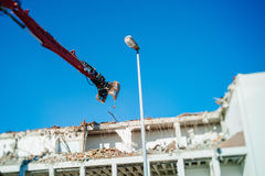 Bulding demolition destruction by the articulating mechanical ja Royalty Free Stock Photos