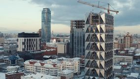 Bulding of new glass skyscraper in the center of large city in winter. Action. Urban landscape, Ekaterinburg, Urals. Bulding of new glass skyscraper in the stock photos