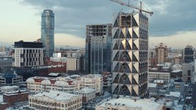 Bulding of new glass skyscraper in the center of large city in winter. Action. Urban landscape, Ekaterinburg, Urals. Bulding of new glass skyscraper in the royalty free stock photos