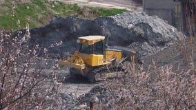 Buldożer pracuje przy rośliną za kwitnącymi drzewami zbiory