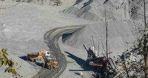Buldożer w łupie ładuje kamień w ciało usyp ciężarówka, budozer żółte pracy w łupie, ładuje usyp zbiory