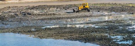 Buldozer giallo che fa i servizi di manutenzione di pulizia e del lago nell'ambito dell'autorità del comune nel tempo di primaver immagine stock libera da diritti