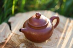 Bule chinês pequeno da argila para a cerimônia de chá na laje de madeira no morni imagem de stock
