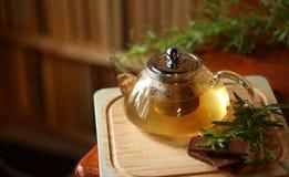 Bule com chá de erva na placa de corte de madeira com alecrins e chocolate próximo, livros no fundo, interior acolhedor da casa Fotografia de Stock Royalty Free