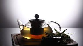 Bule com chá de erva na placa de corte de madeira com alecrins e chocolate próximo, tiro do estúdio Fotografia de Stock Royalty Free