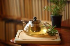 Bule com chá de erva na placa de corte de madeira com alecrins próximo, livros no fundo, interior acolhedor da casa Fotos de Stock