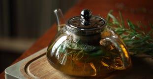 Bule com chá de erva na placa de corte de madeira com alecrins próximo, livros no fundo, interior acolhedor da casa Foto de Stock