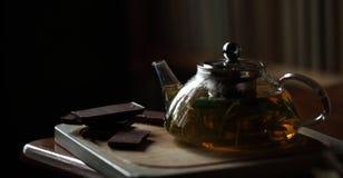 Bule com chá de erva na placa de corte de madeira com chocolate próximo, livros no fundo, noite acolhedor da casa Fotografia de Stock