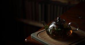 Bule com chá de erva na placa de corte de madeira, interior da casa Imagens de Stock