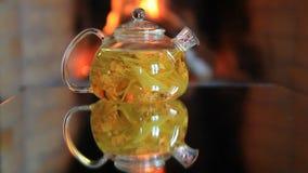 Bule com chá do cal perto da chaminé filme