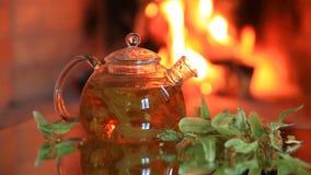 Bule com chá do cal perto da chaminé video estoque