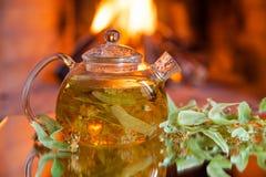 Bule com chá do cal perto da chaminé Imagens de Stock
