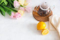 Bule com chá preto, limão e flores na tabela branca Copie o espaço Tea party da mola Vista superior imagens de stock royalty free