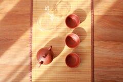 bule, copo de chá e folhas de chá em uma esteira de bambu Fotos de Stock