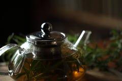 Bule do close up com chá de erva na placa de corte de madeira em casa Imagens de Stock Royalty Free
