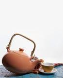 Bule do voo, copo de chá Para derramar o chá Gotas Fundo branco Imagens de Stock Royalty Free