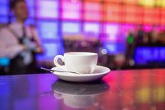 Bule e copo de chá brancos no fundo das luzes da cor Fotografia de Stock Royalty Free
