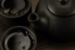 Bule preto, dois copos no fundo de madeira velho Imagem de Stock Royalty Free