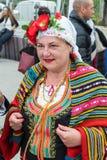 Bulgária, vila dos búlgaros Bordado nacional em um terno do ` s das mulheres em jogos de Nestenar Foto de Stock