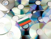 Bulgaarse die vlag bovenop CD en DVD-stapel op wit wordt geïsoleerd Stock Foto