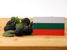 Bulgaarse vlag op een houten die paneel met braambessen op a wordt geïsoleerd Stock Foto's