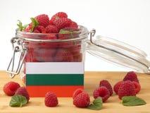 Bulgaarse vlag op een houten die paneel met frambozen op a wordt geïsoleerd Stock Foto