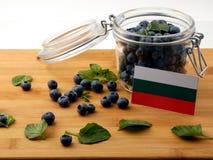 Bulgaarse vlag op een houten plank met bosbessen op wh Stock Foto