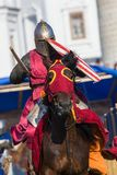 Bulgar, Russian Federation - August 2018, - a man in a knight`s armor and in a Burgundy mantle riding a horse in a stock photos