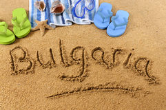 Bulgaria beach. The word Bulgaria written on a sandy beach, with beach towel, starfish and flip flops Stock Image