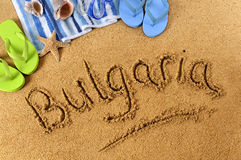 Bulgaria beach writing. The word Bulgaria written on a sandy beach, with beach towel, starfish and flip flops Stock Photo