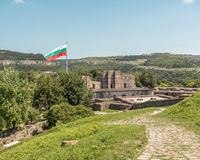 Bulgarian flag flying over ruins of medieval fortress. Tsarevets Royalty Free Stock Image