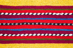 Bulgarian hand woven woollen rug in a bright striped pattern. Bulgarian hand woven woollen rug with a bright multicolored striped pattern and white accents in a Royalty Free Stock Images
